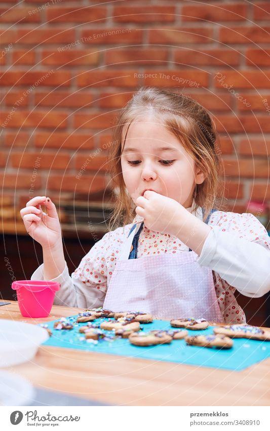 Kind nimmt an Backworkshop teilKleines Mädchen probiert selbst gebackene Kekse. Sie verziert ihre gebackenen Kekse mit bunten Streuseln und Puderzucker. Kind, das am Backworkshop teilnimmt. Backkurse für Kinder, aufstrebende kleine Köche. Kochen lernen