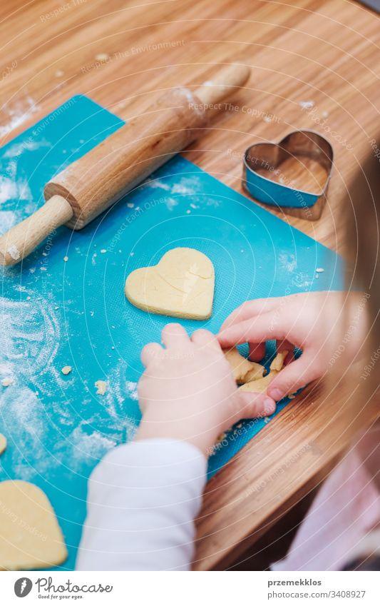 Kleines Mädchen schneidet den Teig für die Kekse in Herzform. Kind, das am Backworkshop teilnimmt. Backkurse für Kinder, aufstrebende kleine Köche. Mädchen, die kochen lernen. Kombinieren und Rühren von vorbereiteten Zutaten. Echte Menschen, authentische Situationen