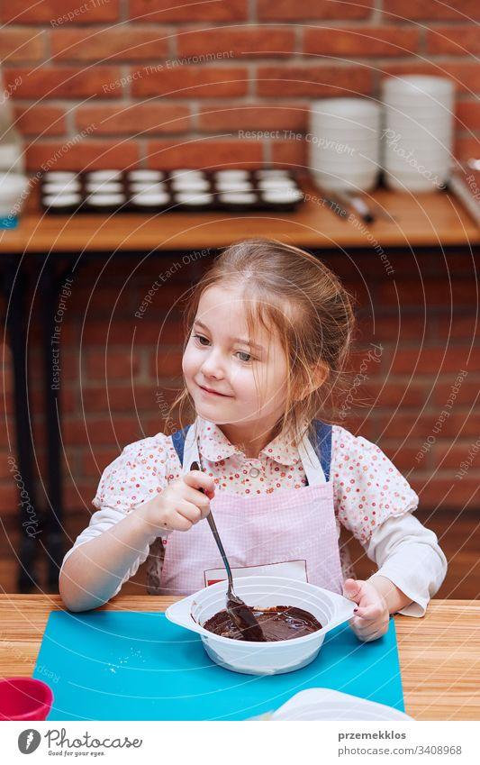 Kleiner Koch, der geschmolzene Schokolade mit Kakao verrührt. Kind, das am Backworkshop teilnimmt. Backkurse für Kinder, aufstrebende kleine Köche. Kochen lernen. Kombinieren und Rühren von zubereiteten Zutaten. Echte Menschen, authentische Situationen