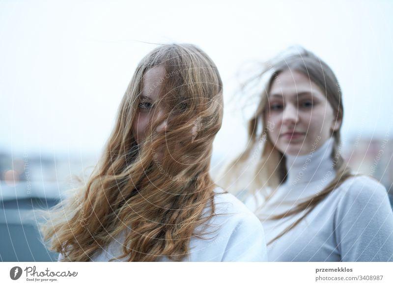 Zwei junge Frauen, die im Freien in die Kamera schauen. Porträt von Mädchen im Teenageralter schön hübsch Freude stylisch niedlich Lächeln Jugend Lifestyle Mode