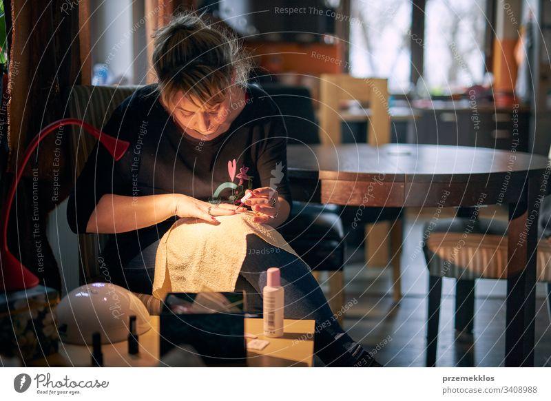 Frau macht Maniküre zu Hause. Keuchende Fingernägel mit Hybrid-Nagellack. Frau, die eine UV-LED-Nagellampe zur Maniküre verwendet. Kosmetik Pflege Nägel