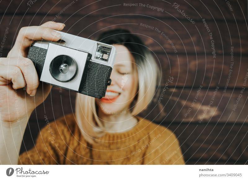 Junge Frau, die mit einer analogen Kamera fotografiert Fotokamera altehrwürdig Fotografie cool trendy retro jung Jugend artits Kunst frisch Frische Ombre Stil