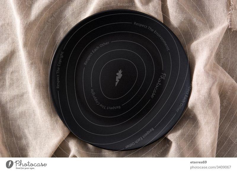 Leere schwarze Platte auf braunem Tuch von oben gesehen Hintergrund Schalen & Schüsseln Geschirr leer Lebensmittel bügeln Küche Attrappe Objekt Teller Schiefer