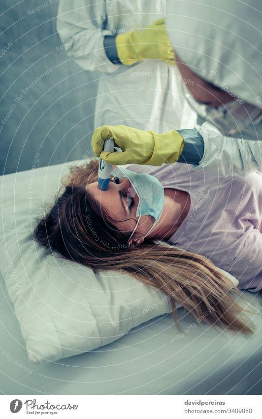Patientin in Begleitung von Ärzten, die prüfen, ob sie Fieber hat Arzt Überprüfung Thermometer Coronavirus COVID19 Symptome covid-19 Krankenhaus Atemwegsvirus