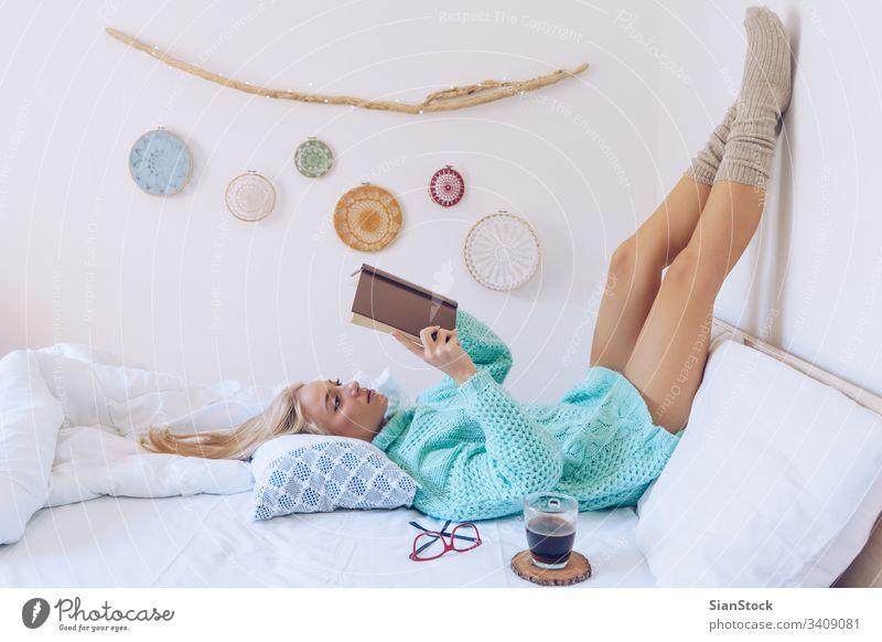 Junge Frau liegt im Bett und liest ein Buch lesen Mädchen Kaffee Pullover weiß schön Brille Morgen heimwärts Schlafzimmer blond Wand Kissen Decke Decken