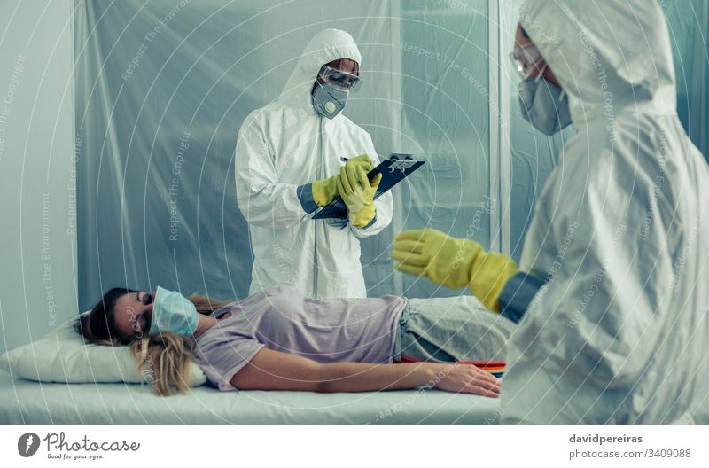 Ärzte mit bakteriologischen Schutzanzügen, die einen Patienten untersuchen Isolation Quarantäne ärztliche Untersuchung covid-19 Coronavirus