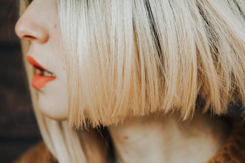 Nahaufnahme der Haare und Lippen einer jungen Frau Frisur sinnlich abschließen Gesicht hübsch blond Behaarung matt Lippenstift Haut Pflege Kosmetik wirklich