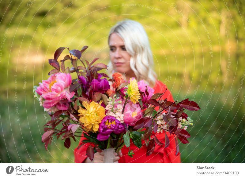 Schöne blonde Blumenhändlerin hält wunderbaren Blumenstrauß Halbprofil Porträt Tag Morgen Begeisterung Euphorie schön Farbfoto Fröhlichkeit Mensch Blüte