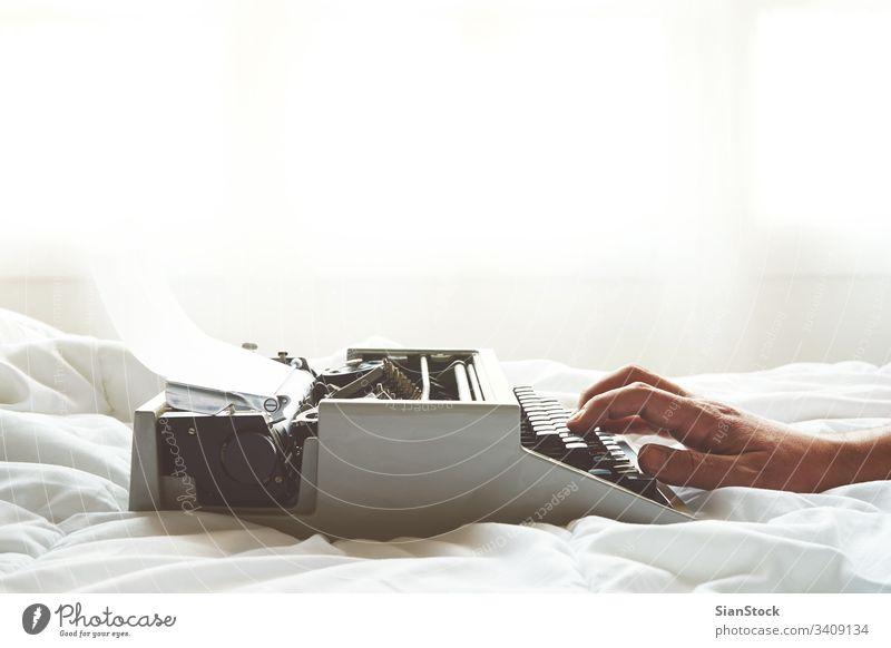 Männer tippen mit den Händen auf einer alten Schreibmaschine auf dem Bett altehrwürdig Schlafzimmer Fenster retro hölzern Papier schreiben Tisch Antiquität Büro