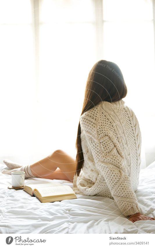 Weiches Foto einer Frau auf dem Bett mit einem alten Buch und einer Tasse Kaffee lesen Fenster Ansicht LAZY Sonntag Winter Tee Morgen Mädchen heimwärts