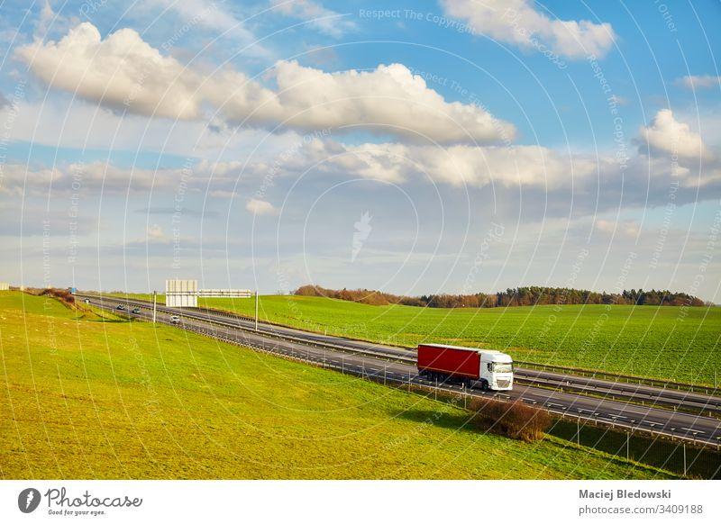 Ländliche Landschaft mit einer Autobahn im Frühling. Lastwagen Verkehr Straße im Freien Lieferkette Güterverkehr & Logistik Lastkraftwagen Laufwerk Anhänger