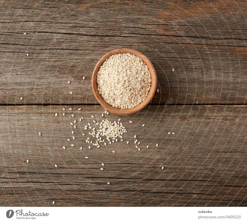 trockene weiße Sesamkörner in einer braunen Holzschüssel Schalen & Schüsseln Lebensmittel Samen Hintergrund organisch Bestandteil hölzern Gesundheit Vegetarier