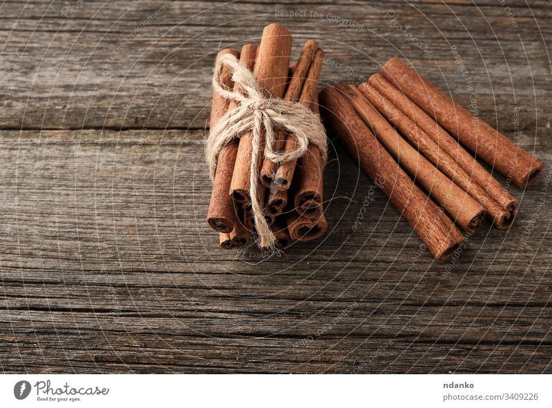 braune Zimtstangen in einem Brötchen gebunden auf grauem Holzgrund, schmackhaftes und duftendes Gewürz Lebensmittel Hintergrund kleben süß hölzern Bestandteil
