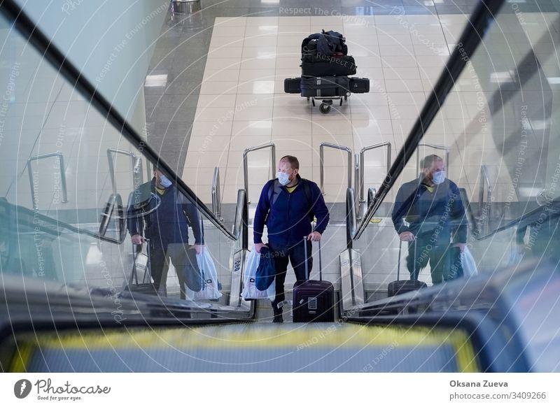 Europäischer Mann mit rotem Bart in blauer Jacke, steigt auf eine Rolltreppe, hat eine medizinische Einweg-Schutzmaske am Flughafen. 2019-ncov ängstlich
