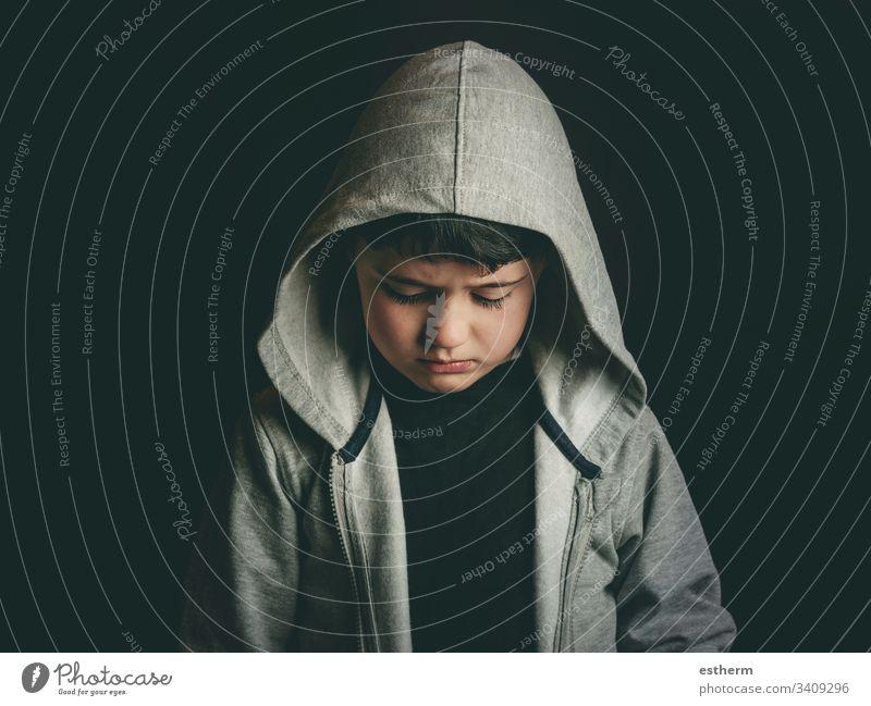 Trauriger Junge auf schwarzem Hintergrund Kind traurig niedergeschlagen Angst unglücklich Mobbing vereinzelt Depression Bildung Stress Opfer Trennung
