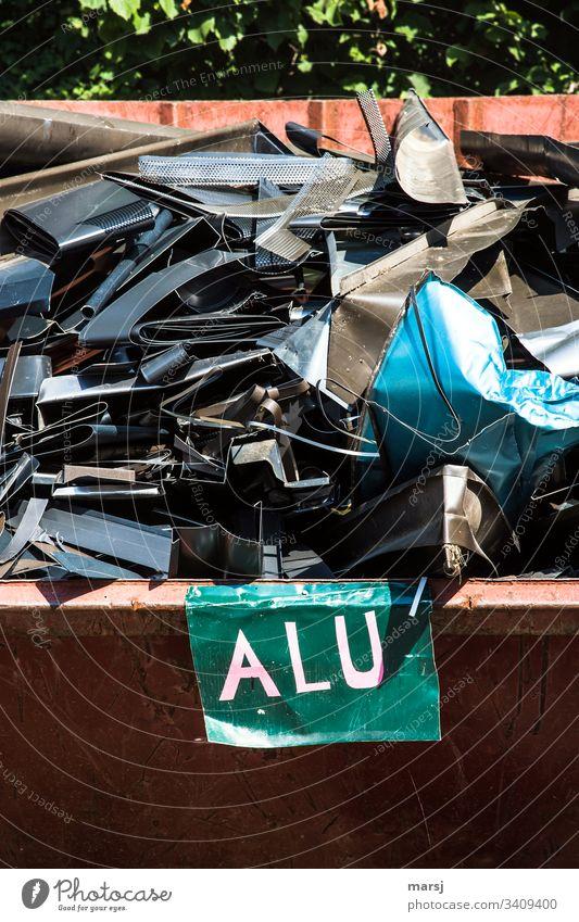 Ein Schrottcontainer voller, teils buntem, Aluschrott eines Dachdeckers. Vorne eine Tafel mit der Beschriftung Alu Aluminium Sammelsurium kunterbunt unbrauchbar