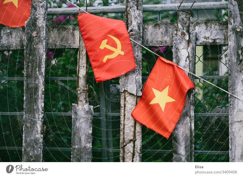 Ein Zaun an dem die vietnamesische Nationalflagge, mit Hammer und Sichel in gelb auf rotem Hintergrund, hängt; Symbol für Kommunismus Flagge Sozialismus Vietnam