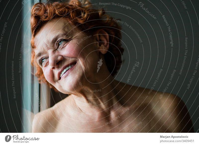 Glückliche reife Frau lächelt am Fenster 60s Erwachsener Lebensalter gealtert Alterung attraktiv schön Schönheit Pflege sorgenfrei Kaukasier charmant heiter