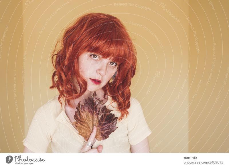 Rothaarige junge Frau, die von einem trockenen Herbstblatt bedeckt ist fallen lassen Blatt Porträt Kunst künstlerisch Rotschopf rote Haare filigran trocknen