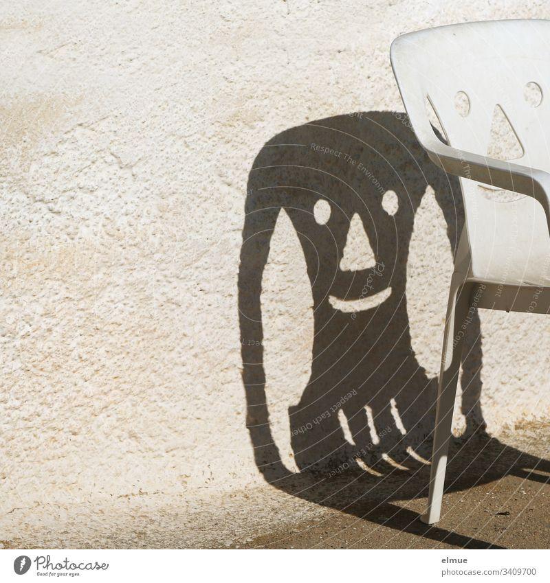 lustiger Schatten eines Plastikstuhles Stuhl Campingstuhl lachen Gesicht Mauer Fröhlichkeit smile Möbel Menschenleer Außenaufnahme Häusliches Leben Gartenstuhl