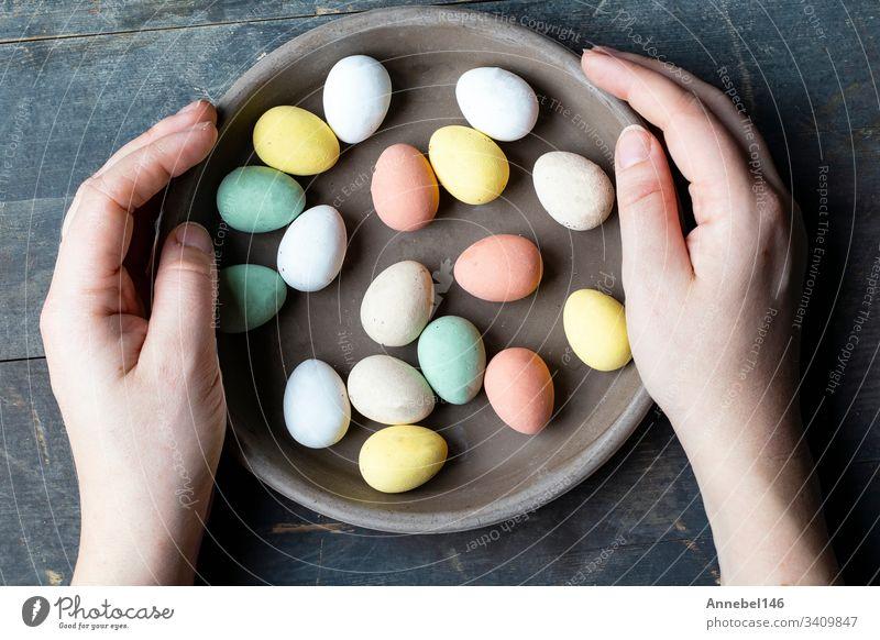 Hände halten stilvolle, pastellfarben bemalte Ostereier in grauer Keramikplatte auf altem Holzgrund, Fröhliche Ostern Feiertag Frühling traditionell Ei Symbol