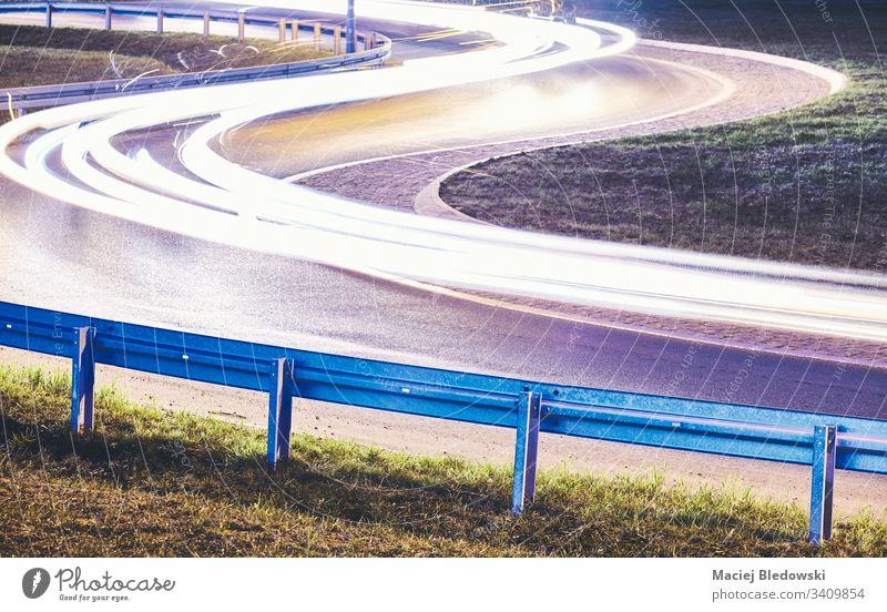 Kurvige Straße mit nächtlichen Autolichtspuren. Nacht Geschwindigkeit Großstadt Laufwerk Leitplanke Sicherheit Autobahn Stahl Gefahr DUI Autoleuchte Barriere
