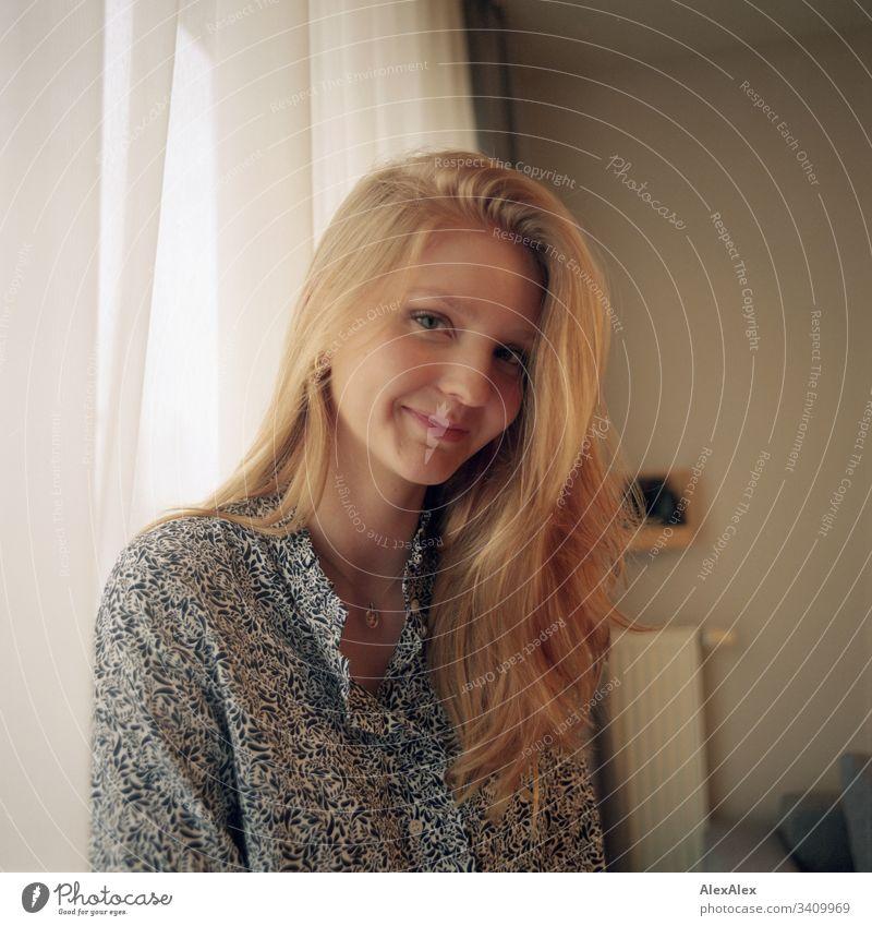 Portrait einer jungen Frau neben dem Fenster an der Gardine Mädchen blond schön schlank anmutig elegant lifestyle Wohnen Wohnung zu Hause Bluse Muster