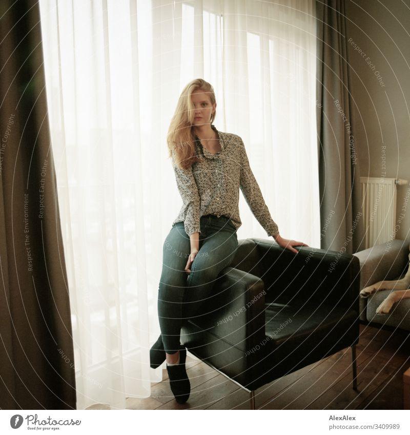 Portrait einer jungen Frau auf einem Sessel vor dem Fenster Mädchen blond schön schlank anmutig elegant lifestyle Wohnen Wohnung zu Hause Gardine Bluse Muster