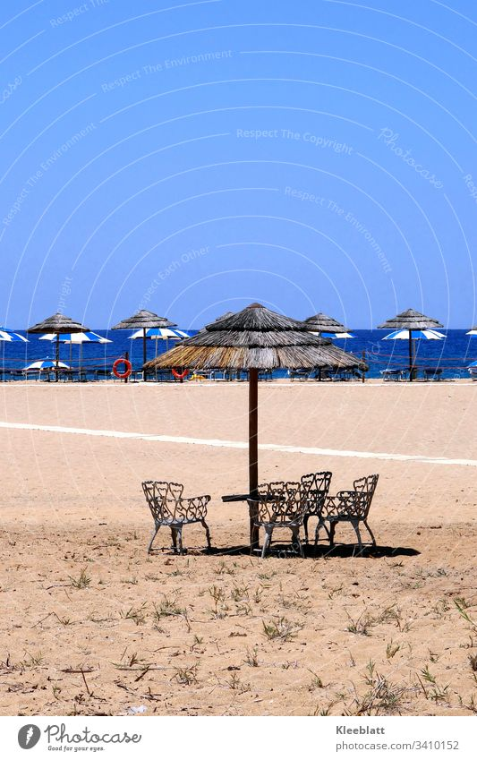 Sandstrand  Stühle Strohsonnenschirme Blau und Beige Ferien & Urlaub & Reisen Sommer Tourismus Meer Erholung Menschenleer Platz an der Sonne Strand