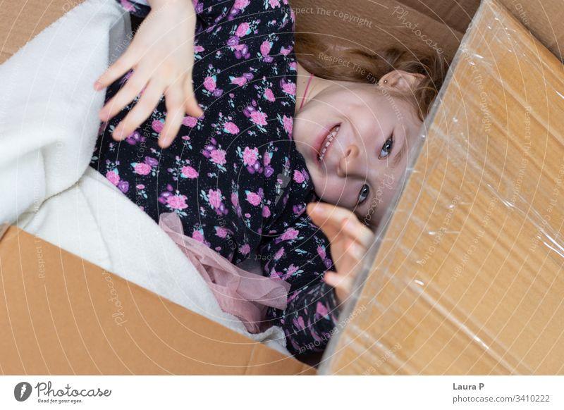 Kleines blondes Mädchen, das sich in einem Pappkarton versteckt einen Blick in die Tasche werfen Versteckspiel Familienspaß Fröhlichkeit Glück genießen Lachen