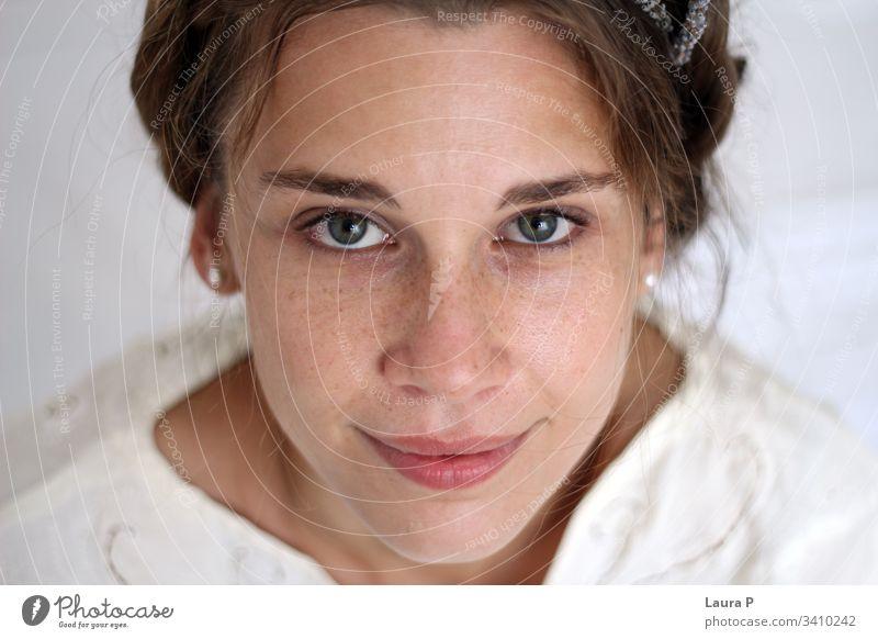 Junge lächelnde Frau mit geflochtenen Haaren, weiß gekleidet jung Gesicht geflochtenes Haar natürliches Aussehen Lächeln abschließen Porträt grüne Augen Kleid
