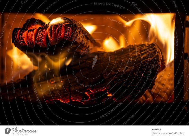 Feuer im Kamin Holzscheit heiß Hitze Flammen gelb schwarz Glut Umweltverschmutzung Kaminfeuer Feuerstelle Brand brennen orange Brennholz heizen glühen