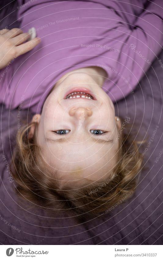 Glückliches kleines Mädchen im Schlafanzug, das im Bett spielt nach unten Kleinkind Lachen Erholung Morgen im Innenbereich Vorschule Tochter bezaubernd Kopf