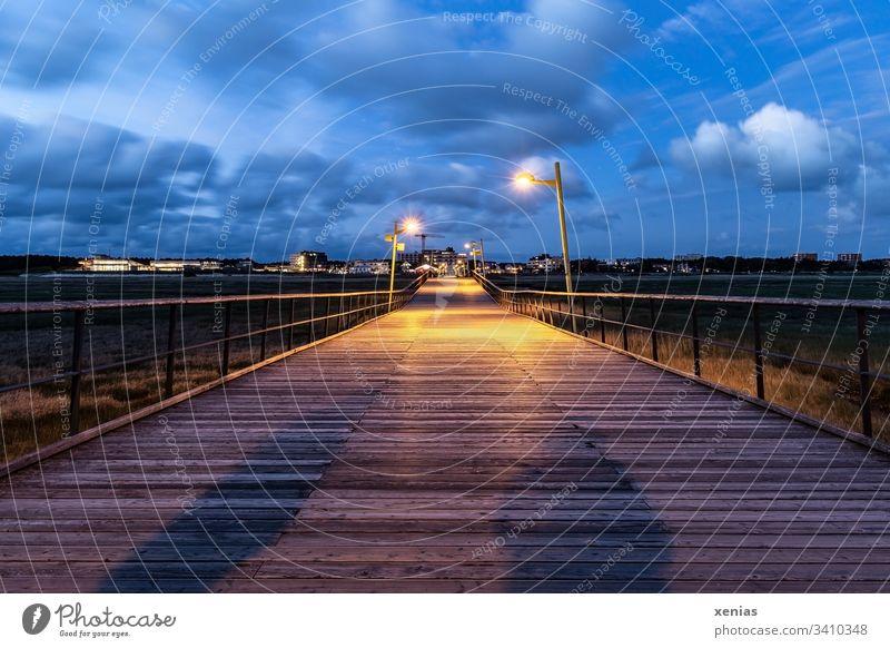 Steg in St.Peter-Ording bei Dämmerung mit großem und kleinem Schatten Holz Brücke Personen Küste blau Himmel Lampen Wolken starke Tiefenschärfe