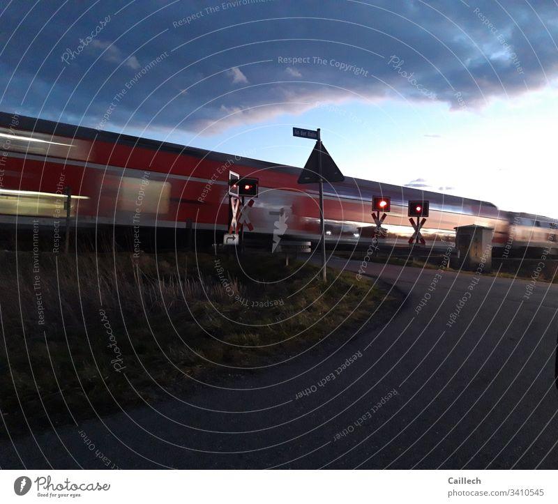 Fahrender Zug am unbeschränkten Bahnübergang Zug, Andreaskreuz, Signal, Bewegung, stopp,frühe Dämmerung Eisenbahn Verkehr Gleise Bahnfahren Außenaufnahme