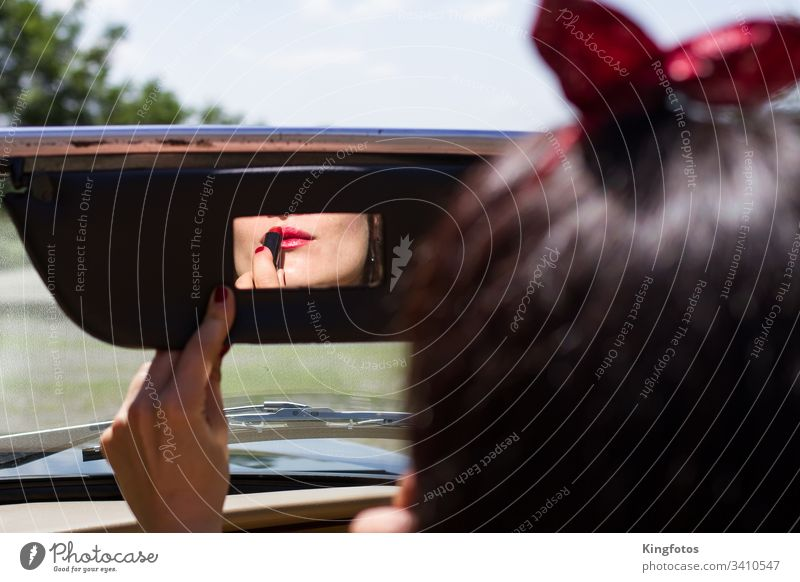 Frau zieht Lippenstift im Auto nach rot Vintage Rückspiegel Autospiegel Schminke Spiegel Cabrio Hand Fingernägel Nagellack Querformat sinnlich Lippenpflege