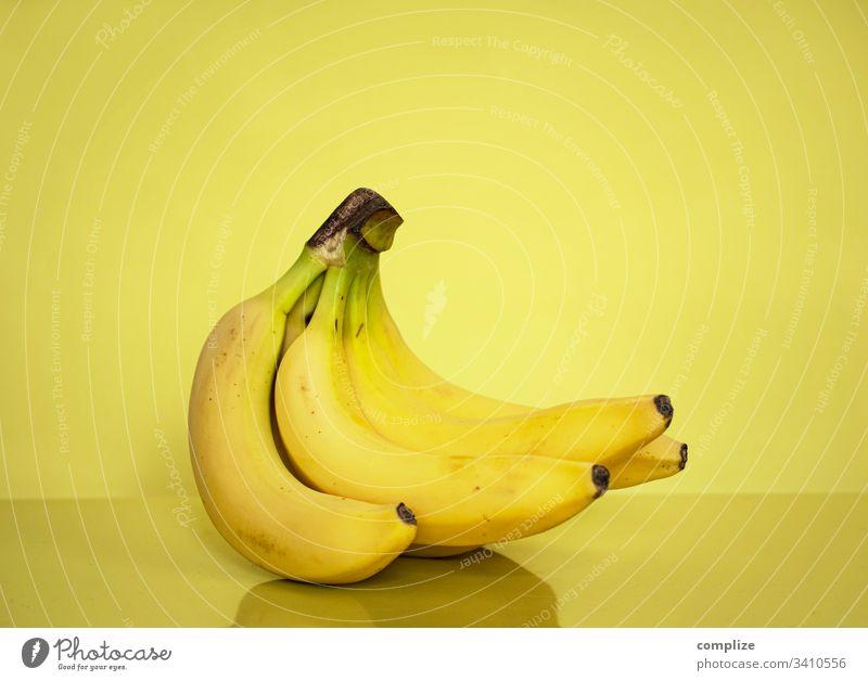 gelbe Bananen vor gelben Hintergrund Gesunde Ernährung Obst- oder Gemüsestand obst früchte südfrucht frisch markt vitamine
