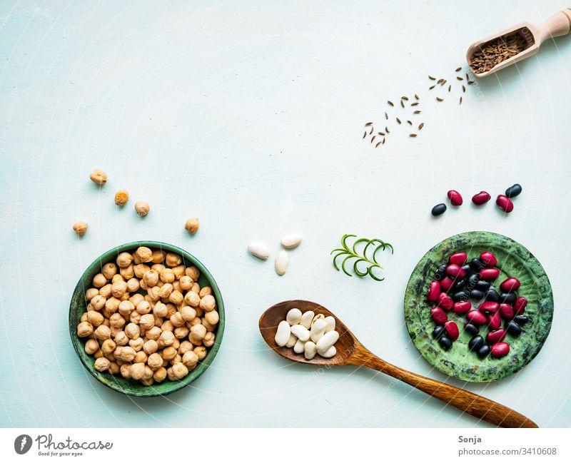 Kichererbsen, verschiedene Hülsenfrüchte und Gewürze auf einem hellgrünen Hintergrund, Flachlage, rustikaler Stil, pflanzliches Eiweiß kichererbsen