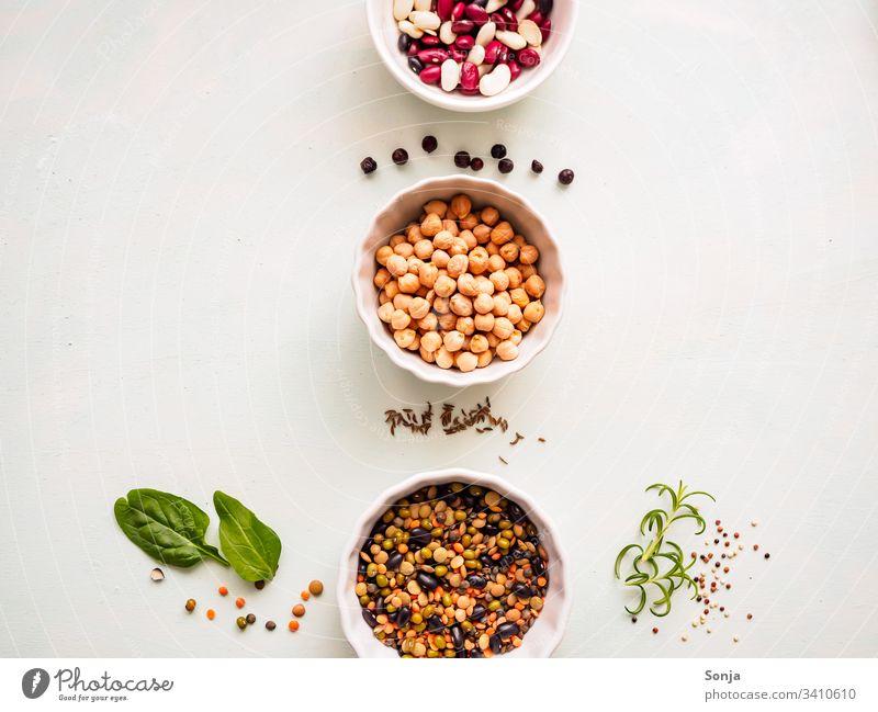 Kichererbsen und verschiedene Hülsenfrüchte in weißen Schüsseln in einer Reihe auf einem hellen Küchentisch mit Gewürzen, Flachlage, pflanzliches Eiweiß, gesunde Ernährung