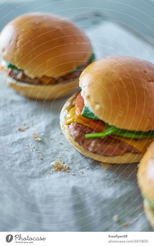 Hausgemachte Hamburger auf Backpapier selbstgemacht backen Koch Essen zubereiten Lebensmittel Gastronomie Tomate Salat Brötchen Fleisch Brot Krümel klassisch