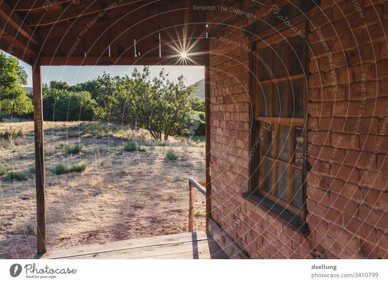 Backsteinhaus mit Holzvordach im Gegenlicht Innenaufnahme ruhig Einfachheit Einsamkeit Starke Tiefenschärfe Sonne Geisterstadt alt braun Spuren Sonnenstern