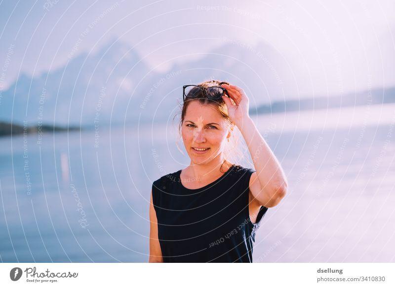 junge Frau im Gegenlicht an einem See mit Bergen im Hintergrund Zufriedenheit Ruhe entspannt Gelassenheit Freude Brillenträger Erholung lachen Farbfoto