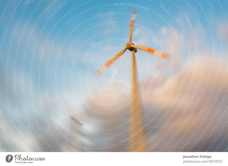 ökologisches Windkraftwerk mit erneuerbarer grüner Energie auf einem Feld in der Abendsonne alternativ Hintergrund blau Unschärfe Wandel & Veränderung