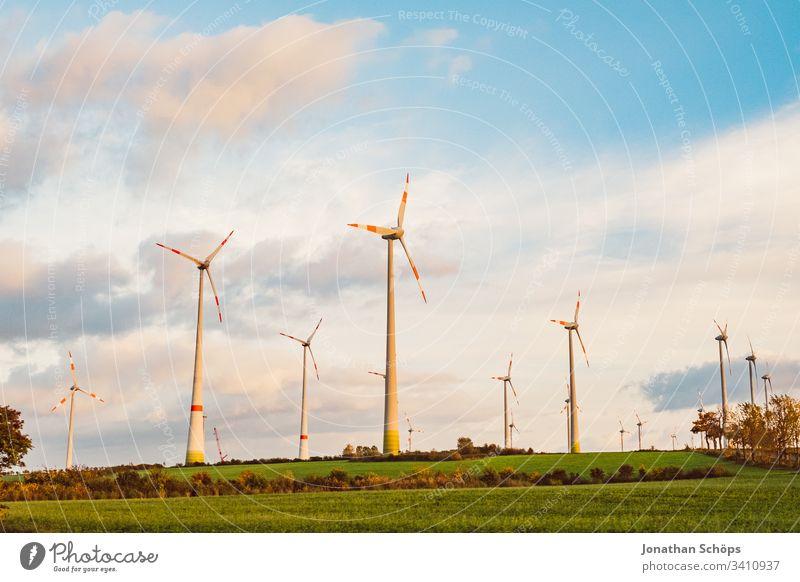 ökologisches Windkraftwerk mit erneuerbarer grüner Energie auf einem Feld in der Abendsonne alternativ Hintergrund blau Wandel & Veränderung Sauberkeit