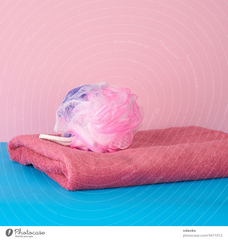 Stapel von rosa gefalteten Handtüchern und einem Plastikwaschlappen auf blauem Hintergrund Bad Schönheit Körper hell Pflege Sauberkeit Nahaufnahme Stoff Farbe