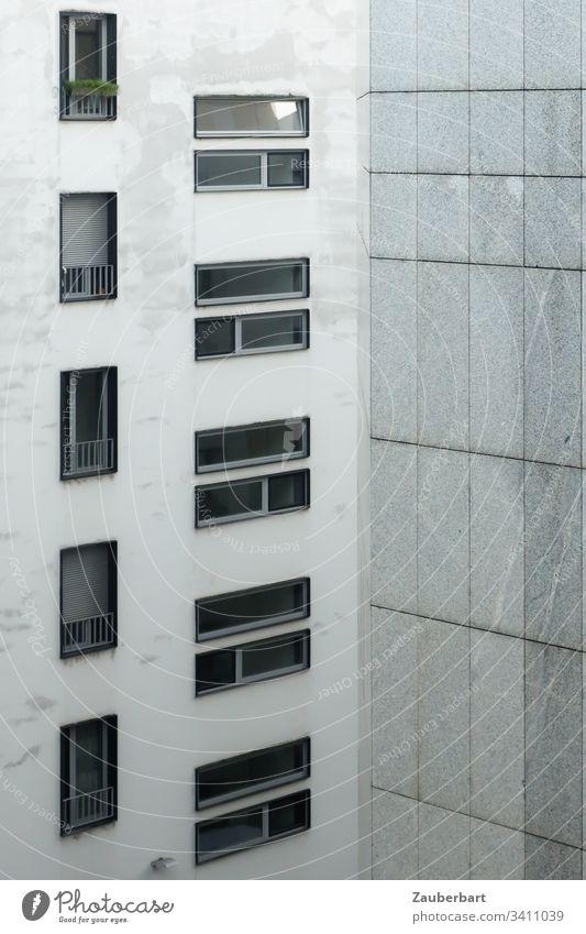 Fassade eines Hochhauses mit Fenstern im Hoch- und Querformat sowie Granitplatten in lichtem Grau Haus Architektur grau lichtgrau trist Fensterrahmen Quarantäne