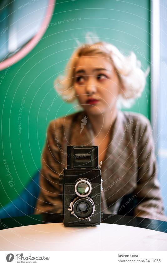 Alte Zweilinsenkamera mit verschwommener weiblicher Silhouette auf der Rückseite, selektive Scharfstellung Schuss Tisch Figur Frau Hand Linse Fotograf