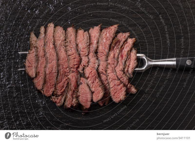 Scheiben eines Steaks auf Schiefer Rindersteak Fleischgabel Metzger Barbecue Aufsicht Fett gegrillt medium geschnitten Gabel Rindfleisch roh fettarm schwarz rot