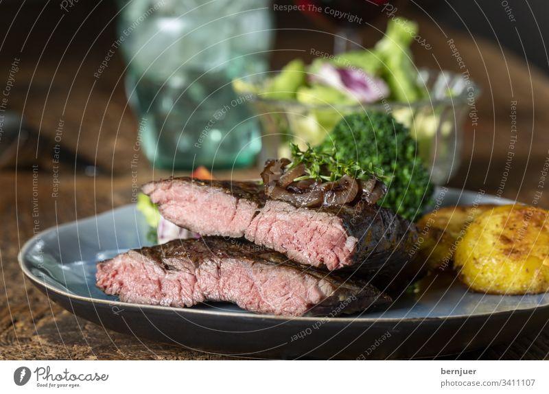 Hälften eines Steaks auf dem Teller Rindersteak Filet argentinisch Hauptgang karamellisiert Zwiebel Nahaufnahme Rinderhüfte saftig lecker Fleisch Essen