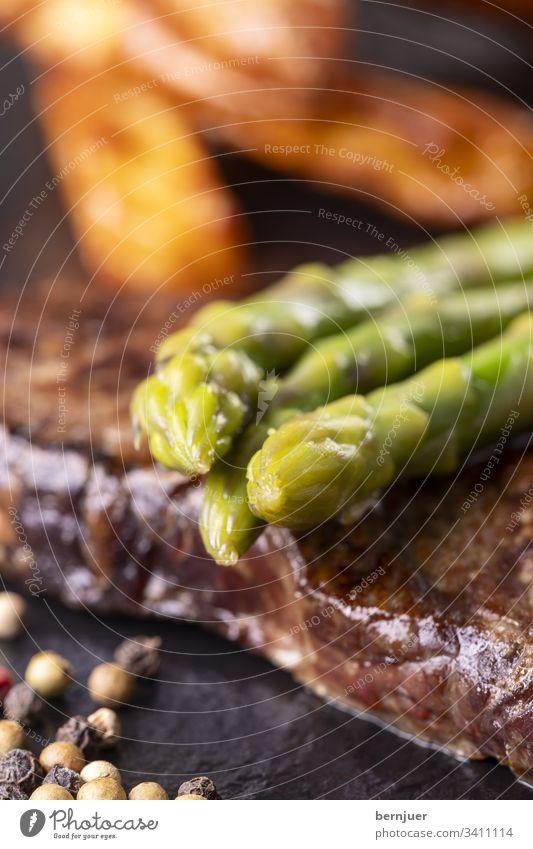 grüner Spargel auf einem Steak Rindersteak Französisch Pfeffer Pfefferkörner Porterhouse fiorentina dry aged Gemüse Kartoffel Kochen Restaurant Nahaufnahme